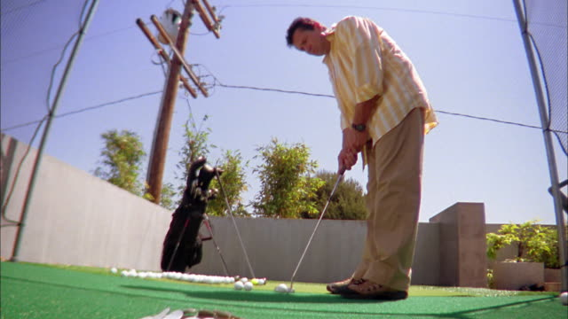 Low angle medium shot man putting golf ball toward CAM on rooftop practice green