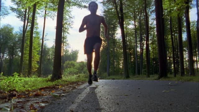 vidéos et rushes de low angle medium shot man running w/out shirt on tree-lined road - seulement des jeunes hommes