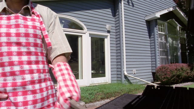 low angle medium shot man scraping grill with children running around in background - oven mitt stock videos and b-roll footage