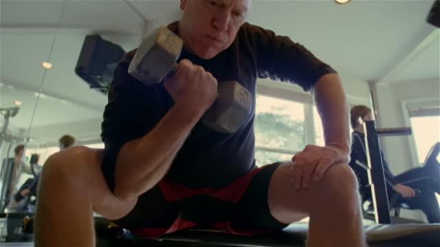 Low angle medium shot man sitting and lifting barbells at gym/ Solebury, Pennsylvania