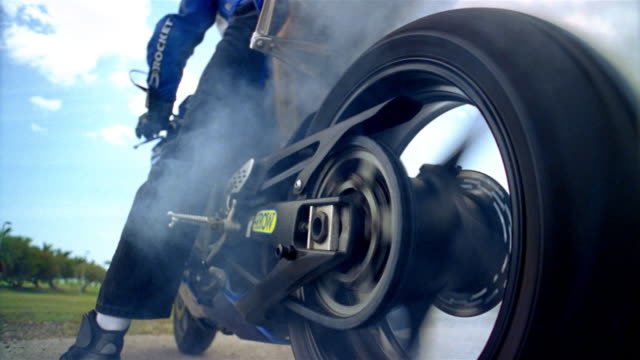 low angle medium shot man sitting on motorcycle as back wheel spins out / smoke billowing up - くるくる回る点の映像素材/bロール