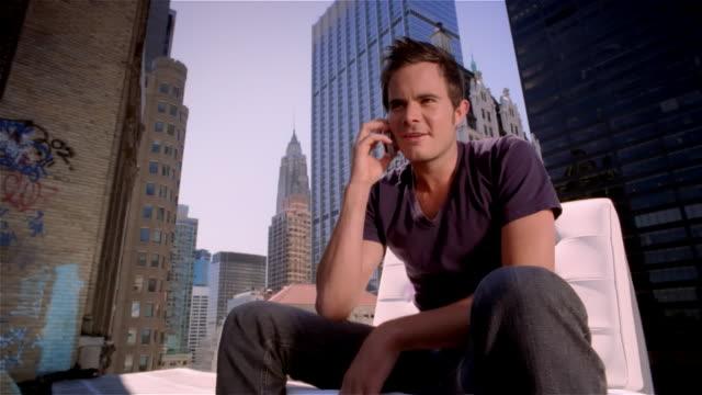 vidéos et rushes de low angle medium shot man sitting on roof answering smart phone / empire state building in background / new york city - seulement des jeunes hommes