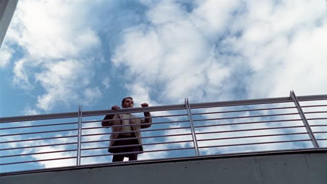 low angle medium shot man standing near railing with cloudy blue sky overhead / berlin - räcke bildbanksvideor och videomaterial från bakom kulisserna