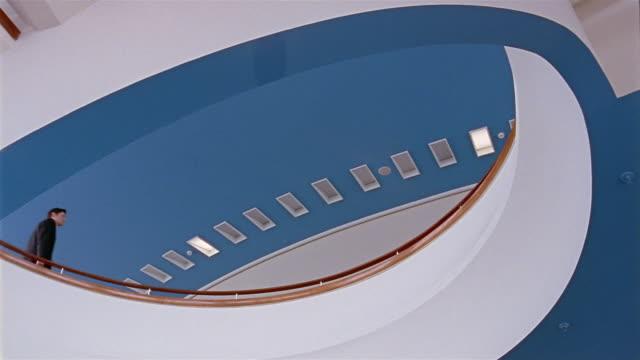 vídeos y material grabado en eventos de stock de low angle medium shot man walking beside landing - interiores modelos