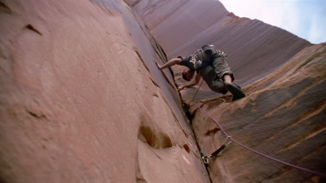 Low angle medium shot man wearing harness and rope climbing rock / searching for hand hold in crevice