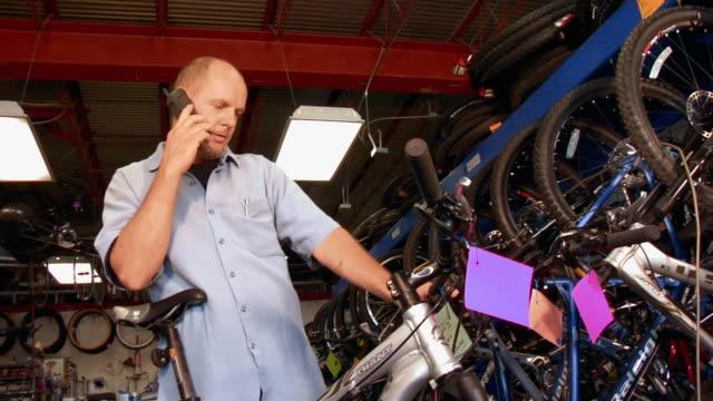Low Angle Medium Shot Man Working At Bike Shop Looking At
