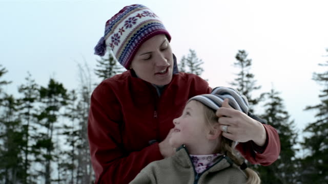 Low angle medium shot mother putting winter hat on daughter's head / woman and girl hugging