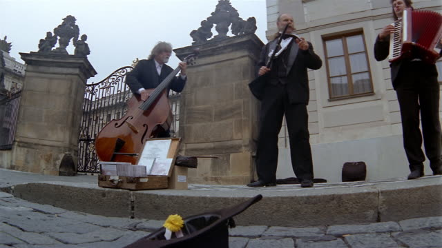 low angle medium shot muscians performing on the street / man putting money into hat / prague - gratuity stock videos & royalty-free footage