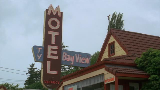 low angle medium shot neon motel sign - motel stock videos & royalty-free footage