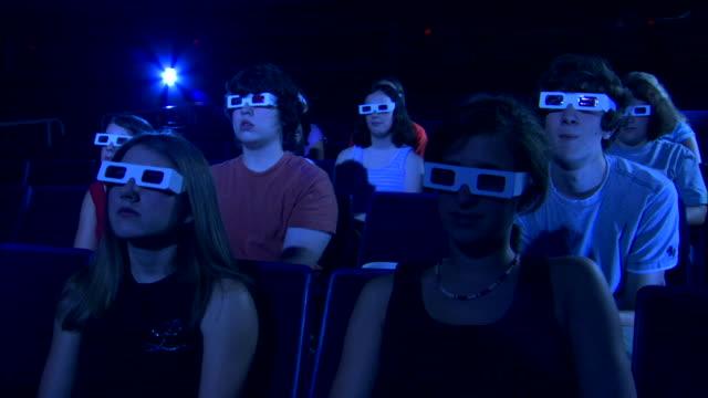 low angle medium shot of a group of people watching a 3d movie. - biosalong bildbanksvideor och videomaterial från bakom kulisserna