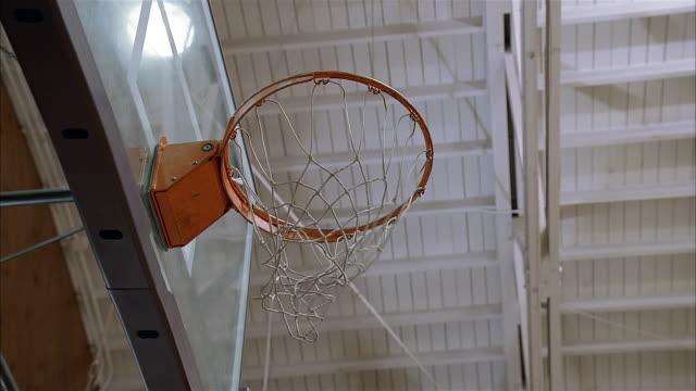 vídeos y material grabado en eventos de stock de low angle medium shot of basketball net / basketball going through net / scoring again - encestar