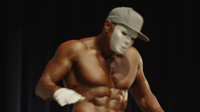 low angle medium shot of bodybuilder miming on stage at competition / draper, utah, united states - baseballmütze stock-videos und b-roll-filmmaterial