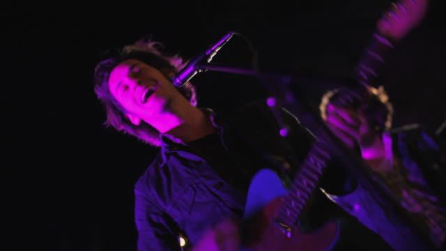 vidéos et rushes de low angle medium shot of lead singer finishing concert - singer