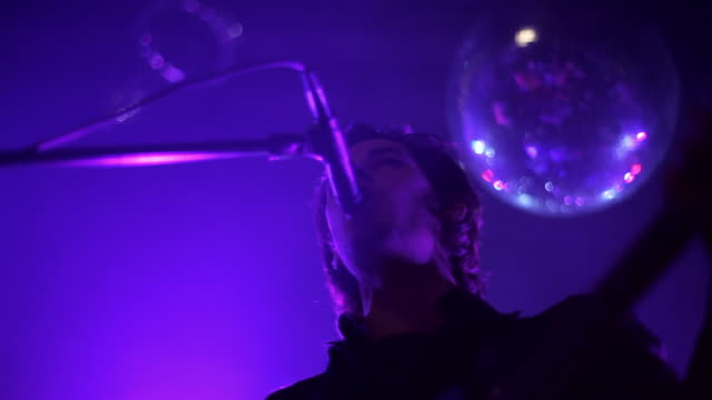 low angle medium shot of lead singer performing on stage - gesangskunst stock-videos und b-roll-filmmaterial