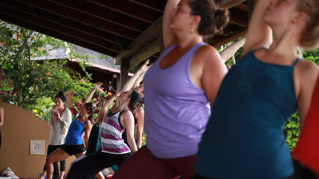 low angle medium shot of women practising yoga and colourful yoga attire and an outdoor yoga tech deck surrounded by lush green vegetation - kelly mason videos stock videos & royalty-free footage