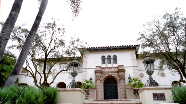 Low angle medium shot palm tree / tilt down to front of large Spanish-style mansion / Beverly Hills, California