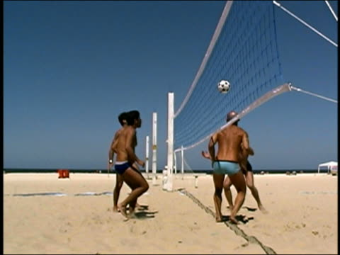 low angle medium shot pan beach volleyball four men heading the ball while playing beach volleyball - volleyballnetz stock-videos und b-roll-filmmaterial