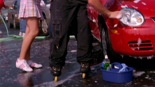 low angle medium shot pan boy on rollerskates skating past girl while washing car - car wash stock videos & royalty-free footage