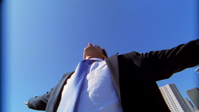 low angle medium shot pan businessman with arms spread outdoors - londonalight点の映像素材/bロール