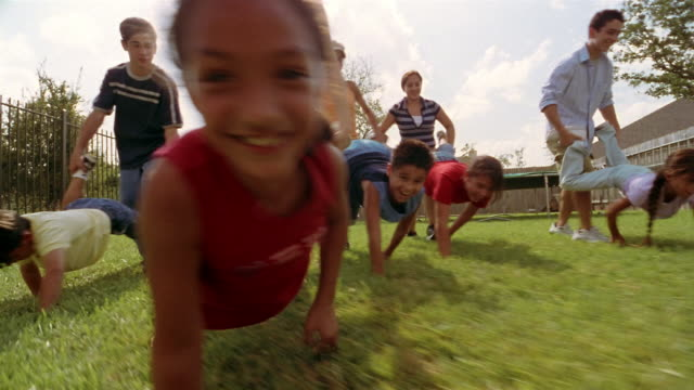 low angle medium shot pan children having wheelbarrow race in backyard - wheelbarrow stock videos and b-roll footage