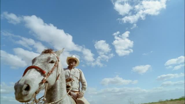 Low angle medium shot pan cowboy climbing onto horse/ Edinburg, Texas