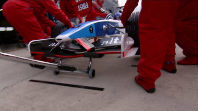 low angle medium shot pan pit crew changing tires on formula one race car during pit stop - formula one racing stock videos & royalty-free footage