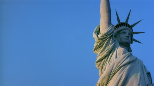 Low angle medium shot pan Statue of Liberty against clear blue sky / New York City