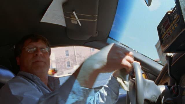 vídeos de stock, filmes e b-roll de low angle medium shot pan taxi driver handing receipt and change towards backseat / nyc - táxi