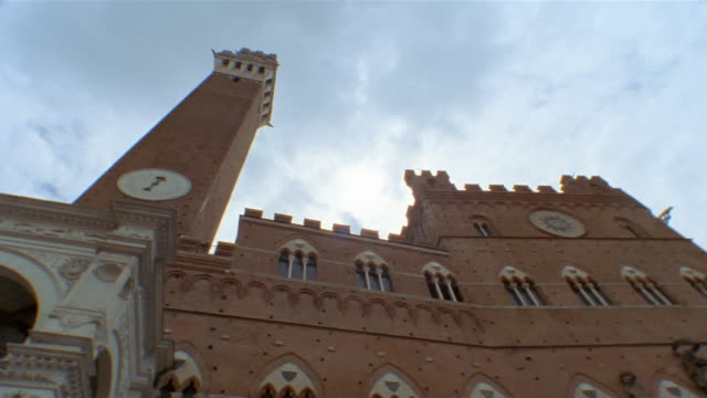 low angle medium shot pan view of the palazzo publico and the torre del mangia in siena, tuscany, italy - palazzo pubblico stock videos and b-roll footage