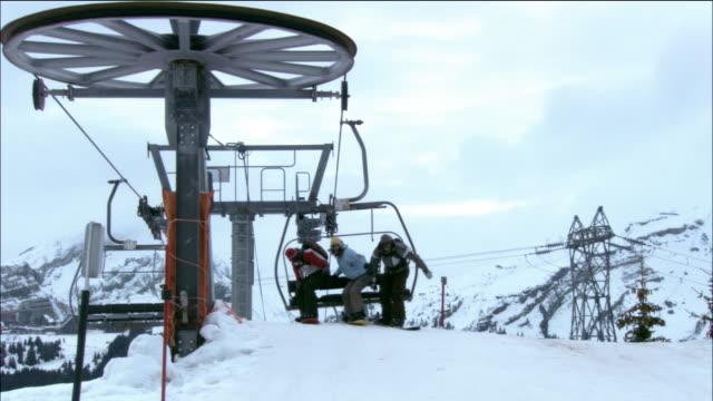vídeos de stock, filmes e b-roll de low angle medium shot pan woman and two men snowboard off ski lift onto top of mountain / morzine, france - roupa de esqui