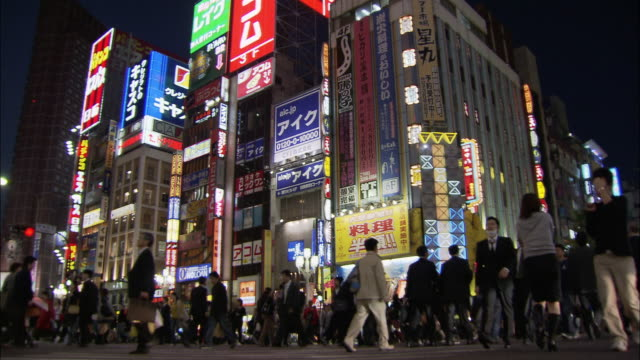 Low angle medium shot pedestrians crossing intersection in Shinjuku at night / Tokyo, Japan