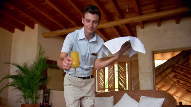 low angle medium shot point of view waiter setting drink and plate of fruit on table in hotel room + smiling at cam - hotel room stock videos & royalty-free footage