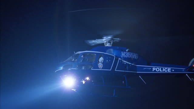 low angle medium shot police helicopter hovering with spotlight on / night / new york city - hubschrauber stock-videos und b-roll-filmmaterial