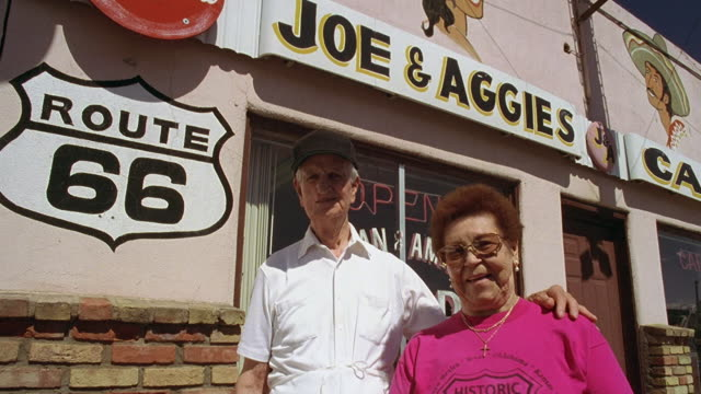 low angle medium shot portrait senior couple standing outdoors by route 66 sign and cafe / arizona - schild stock-videos und b-roll-filmmaterial