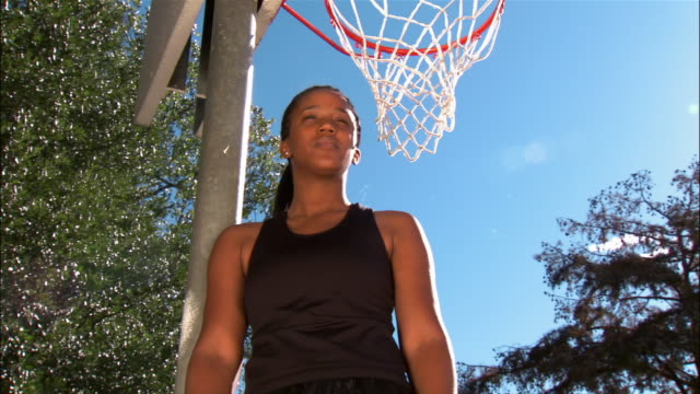 low angle medium shot portrait woman standing under basketball net and catching basketball/ dallas, texas - tank top stock videos & royalty-free footage