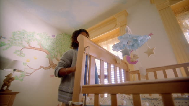 Low angle medium shot pregnant Black woman adjusts mobile above crib in nursery / man hugs her and feels stomach