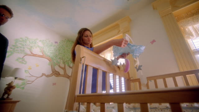 Low angle medium shot pregnant woman adjusts mobile above crib in nursery / man hugs her and feels stomach