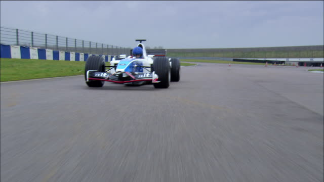 stockvideo's en b-roll-footage met low angle medium shot rear point of view formula one race car riding around race track - racewagen