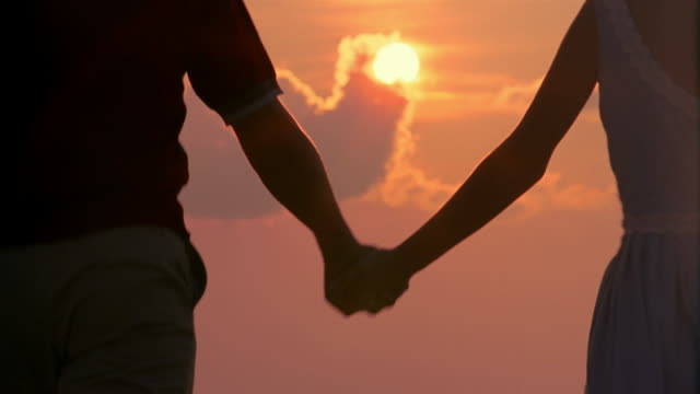 low angle medium shot reconstruction teenage couple holding hands and walking with sunset in background / miami, fl - teenagerpaar stock-videos und b-roll-filmmaterial