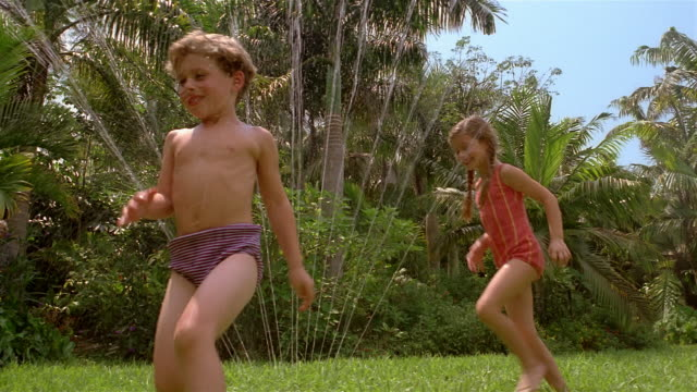 vídeos de stock, filmes e b-roll de low angle medium shot reconstruction young boy and girl running through sprinkler / miami, florida - roupa de natação