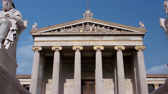vidéos et rushes de low angle medium shot relief in pediment on roof / zoom out steps and sculptures in front of athens academy / athens, greece - fronton
