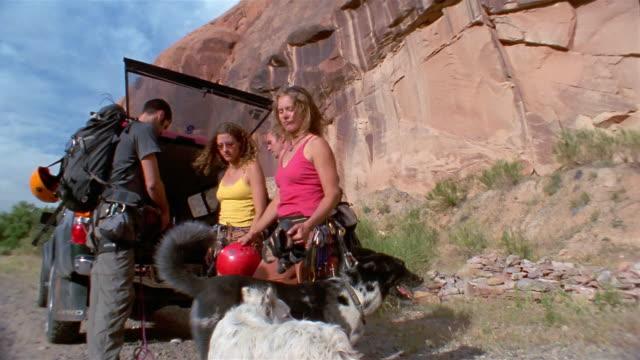 vídeos y material grabado en eventos de stock de low angle medium shot rock climbers unloading equipment form car / rock in background - maletero