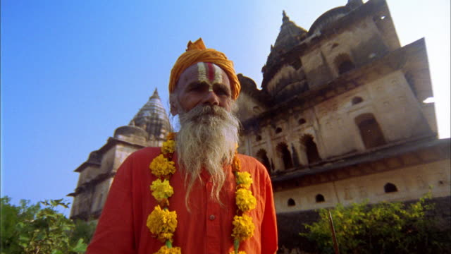 low angle medium shot sadhu holy man (hindu) posing in front of temple / orchha, india - einzelner senior stock-videos und b-roll-filmmaterial