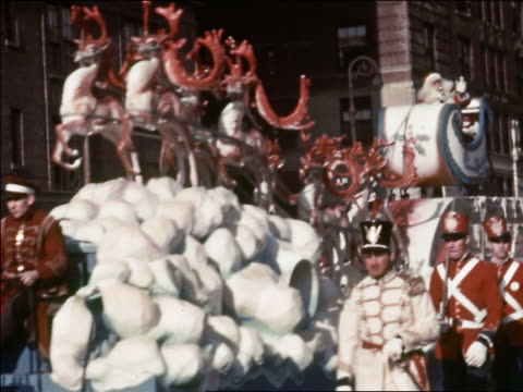 1941 low angle medium shot Santa Claus riding in sleigh on float in Macy's Thanksgiving Day Parade / New York City