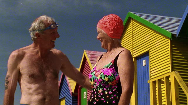 low angle medium shot senior couple in swimsuits hugging by beach houses / st. james beach, cape town, south africa - brusthaar stock-videos und b-roll-filmmaterial