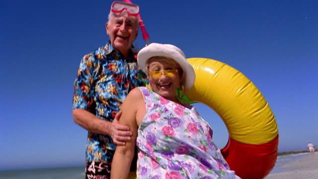 vídeos de stock, filmes e b-roll de low angle medium shot senior couple posing on beach with raft and man wearing snorkel / florida - jovem de espírito