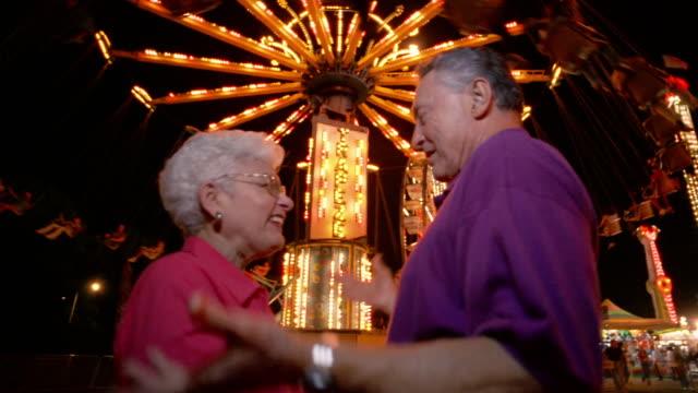 low angle medium shot senior couple watching ride at amusement park at night - 遊園地点の映像素材/bロール