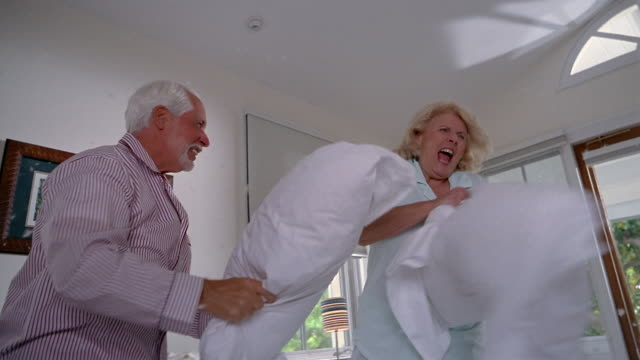 vidéos et rushes de low angle medium shot senior man and senior woman having pillow fight on bed / feathers flying / miami, florida - espièglerie