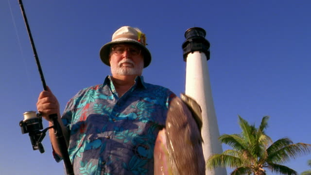 Low angle medium shot senior man holding up line of fish / lighthouse in background