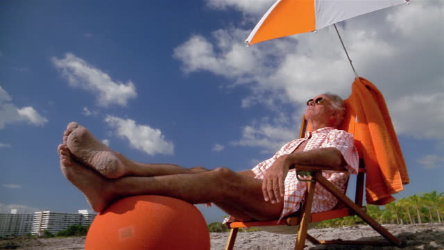 low angle medium shot senior man sitting under umbrella beach chair with his feet up on foot rest with blue sky in background - gulf coast states stock-videos und b-roll-filmmaterial